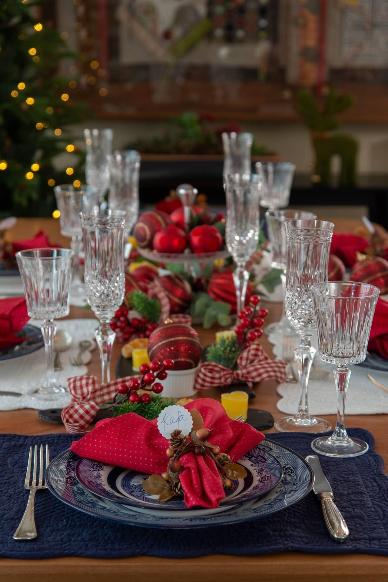 """Imagem: A combinação da Blue Willow, da Oxford, com os enfeites vermelhos dá um ar de inusitado à mesa de Natal. As taças de cristal lapidado seguem a tendência mix &amp; match. A taça de espumante é da <a href=""""https://www.strauss.com.br/linha/classicos/"""">Strauss</a> (modelo 237.007.068). E a taça de vinho é da Biona, à venda em revendedores de todo país. Foto: Cacá Bratke"""