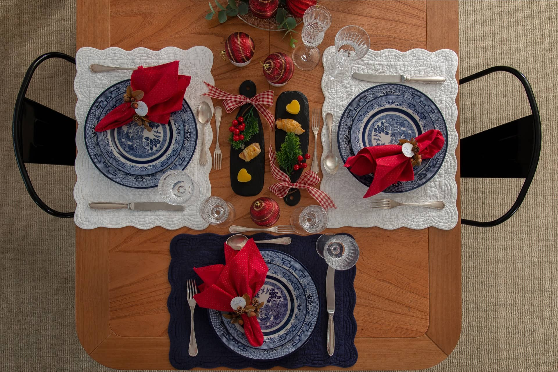 Imagem: Os jogos americanos de algodão matelassê, em branco ou azul marinho, combinam com as louças Blue Willow da Oxford Porcelanas. E contrastam com os enfeites natalinos e os guardanapos vermelhos. Foto: Cacá Bratke