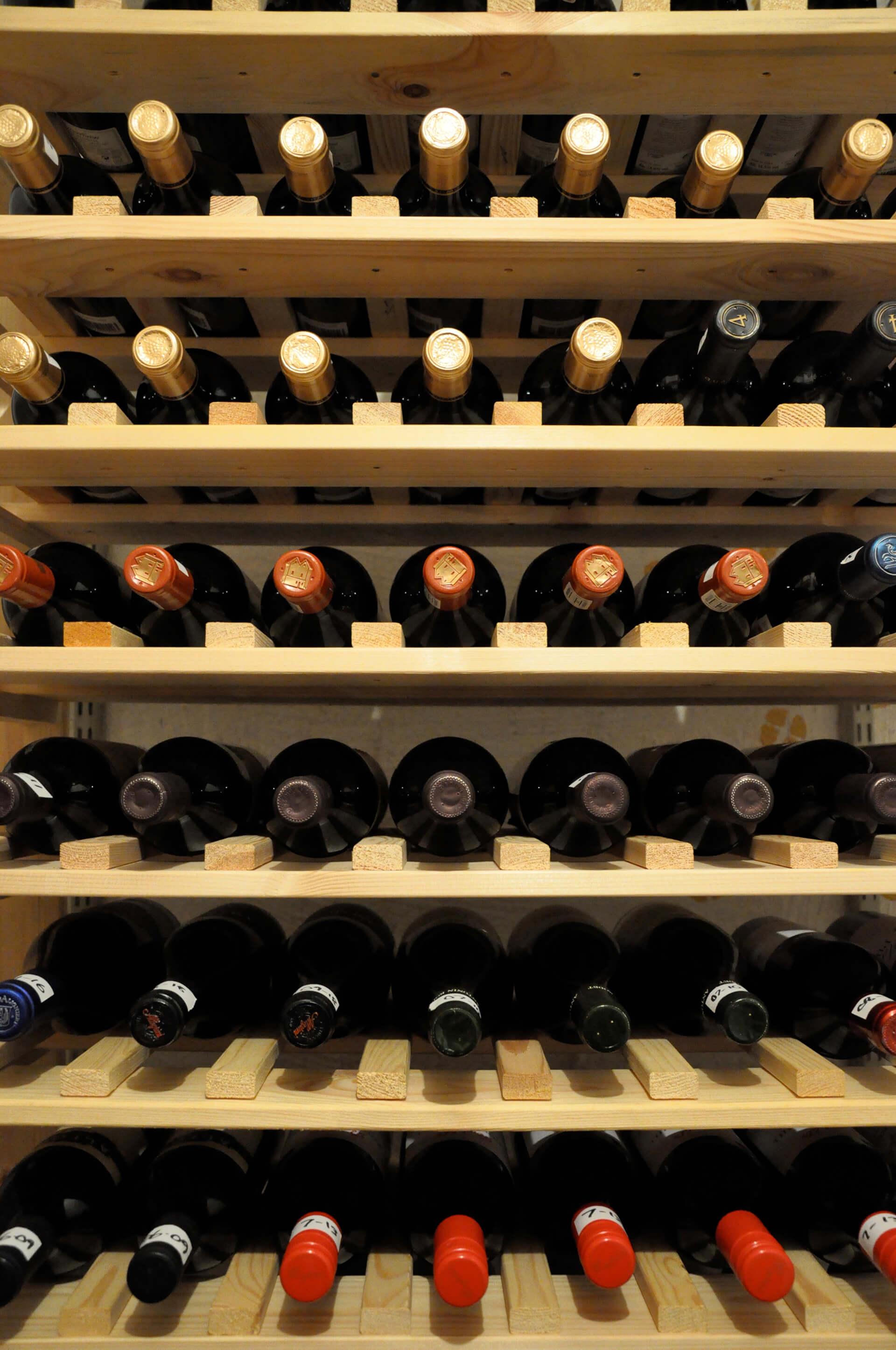 Solução criativa e barata para deixar a adega organizada: prateleiras de madeira com ripas entre as garrafas.