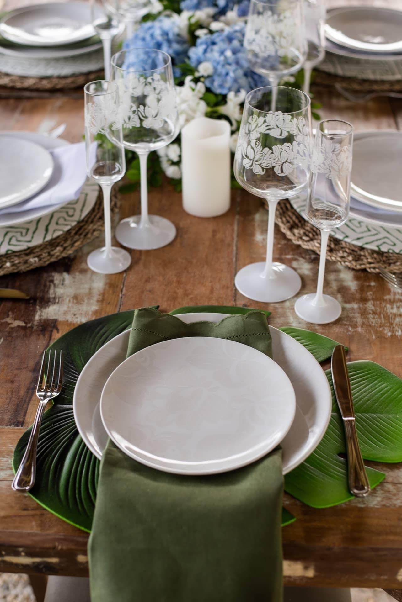 Imagem: Nas cabeceiras da mesa, os sousplats são diferentes dos demais: têm formato de folha, em harmonia com o clima campestre do almoço de casamento. Foto: Karla Rudnick/Produção: Ateliê da Mesa