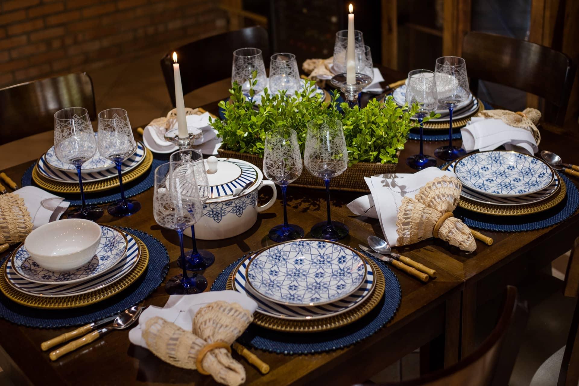 Imagem: No jantarzinho chique, os arabescos da louça portuguesa e as listras em tom de azul cobalto atualizam o jogo de jantar Coup Lusitana da Oxford Porcelanas. Foto: Karla Rudnick. Produção: Ateliê da Mesa