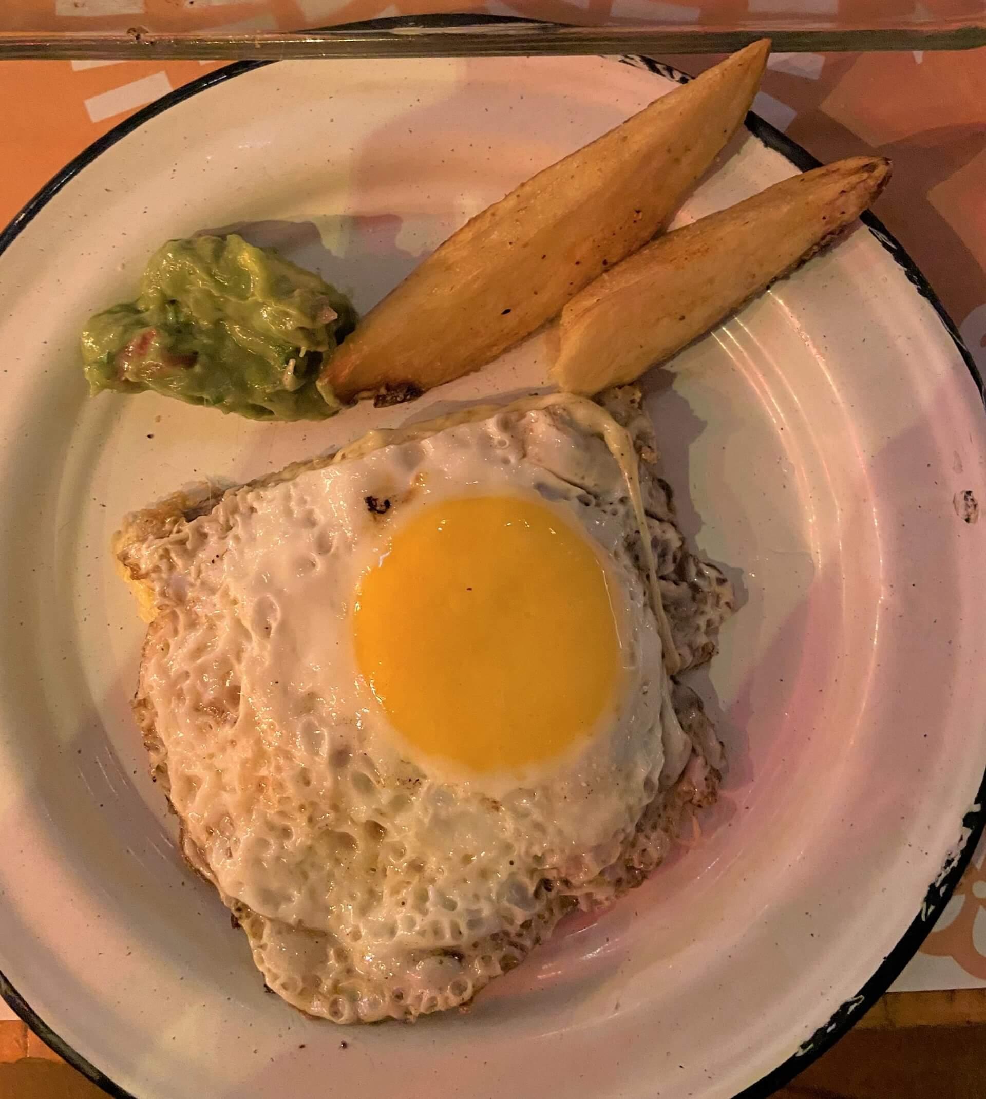 Milanesa com ovo de gema mole, acompanha guacamole, creme azedo (sour cream) e batatas. Foto: Fabíola Cordeiro.