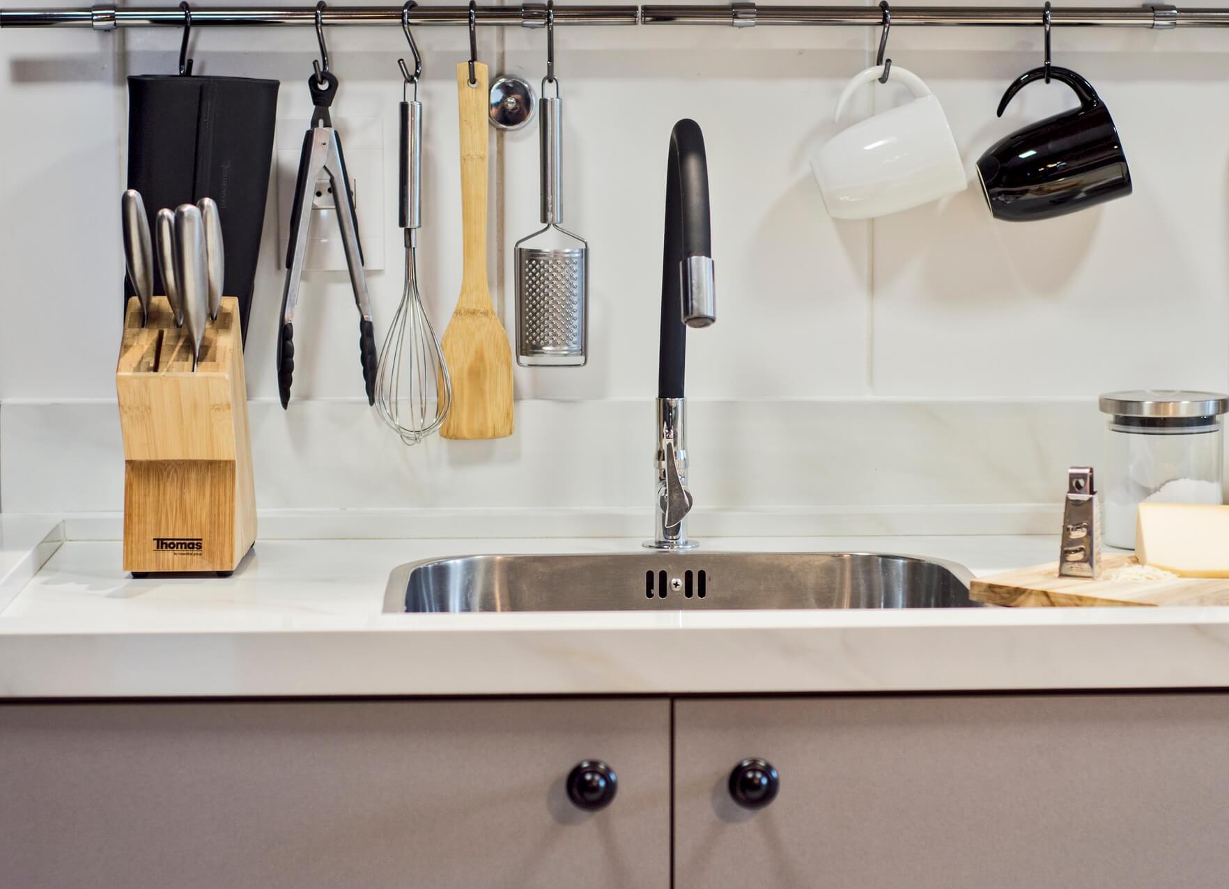 Um elemento que é muito útil e traz uma cara industrial para a cozinha é a barra de utensílios. Projeto: Arquiteca Projetos. Foto: Nadya Costa.