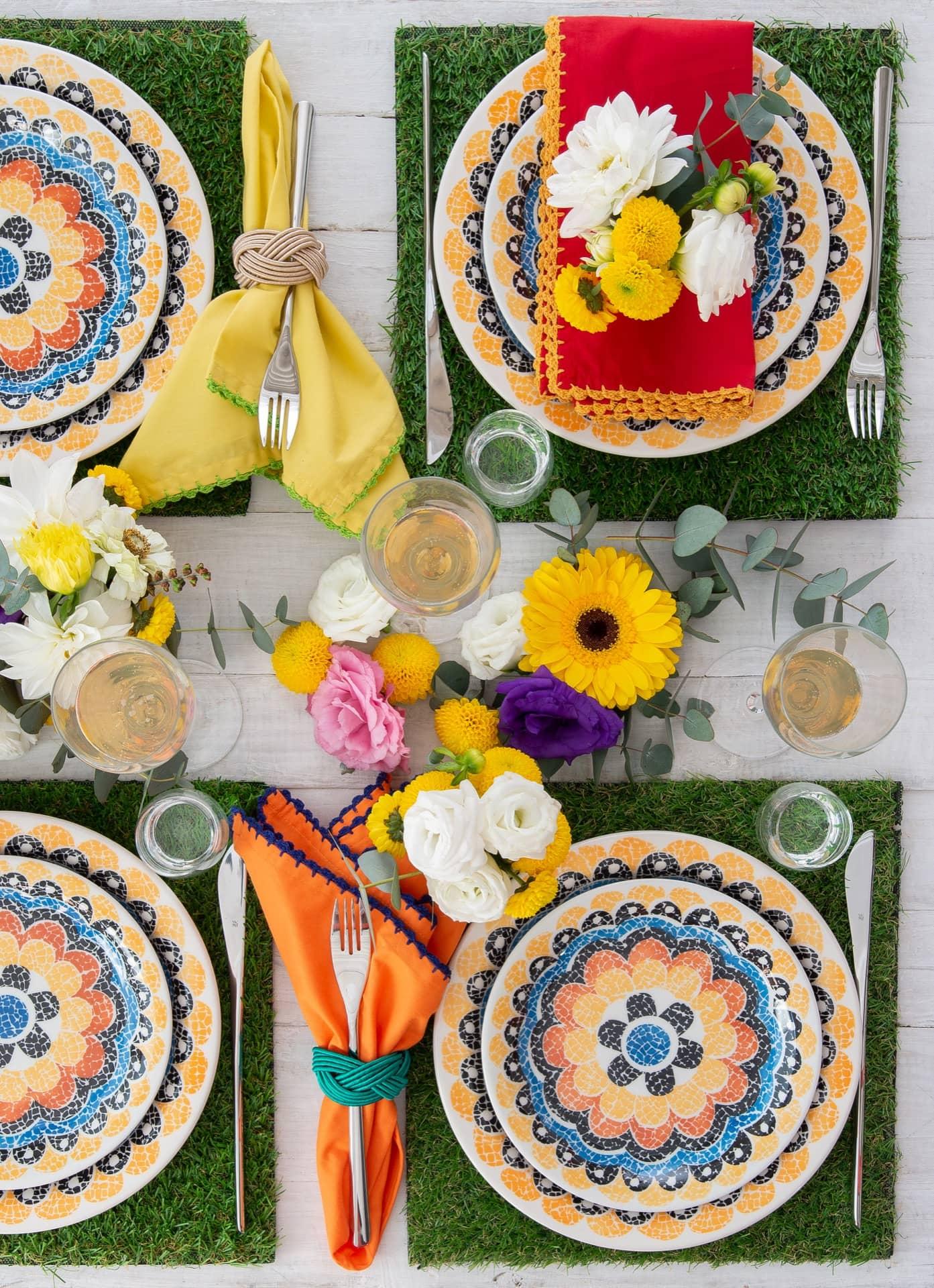 """Nessa mesa festiva e florida, o garfo fica dentro no anel de guardanapo. O jogo de jantar é Floreal Summer da Oxford Daily. E o jogo americano, de grama sintética, é da Villa Pano. Foto: <a href=""""https://www.instagram.com/cacabratke/"""">Cacá Bratke</a>. Realização: <a href=""""https://www.instagram.com/chezpixu/"""">Pixu</a>"""