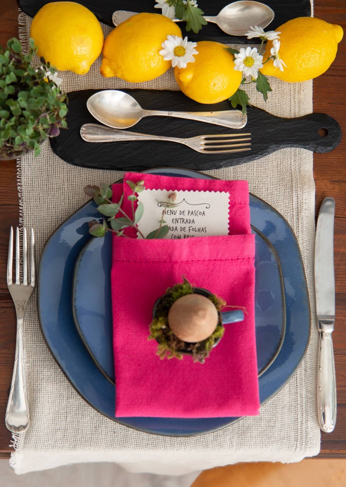Que tal colocar o menu do almoço dentro do guardanapo, junto com um ramo de eucalipto? Nesta mesa de Páscoa, a xícara de café também vira enfeite: acomoda um punhado de musgo e um ovo de madeira. Aparelho de jantar Ryo Santorini da Oxford. Foto: Cacá Bratke. Realização: Pixu