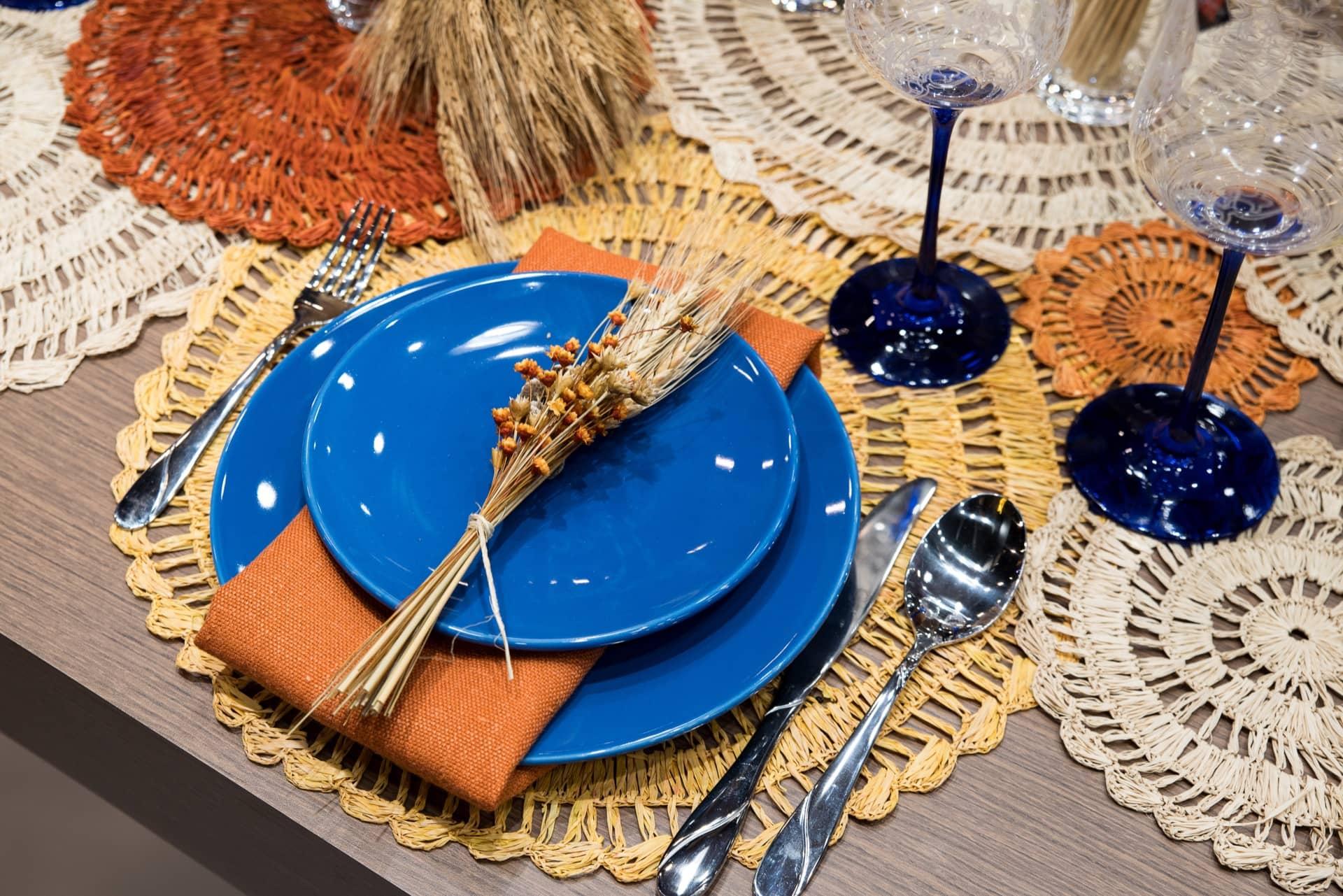 """As flores secas, super em alta na decoração, ficam sobre o prato da entrada, amarradas num delicado buquê. O guardanapo, em tom terroso, envolve o prato de jantar. Toalhinhas de palha, em vários tons naturais, reforçam o estilo rústico da mesa. Os pratos de cerâmica são da linha Unni da Oxford. Foto: Henrique Peron. Realização: <a href=""""https://www.instagram.com/lardocecasa/"""">Giselle Martos</a>"""