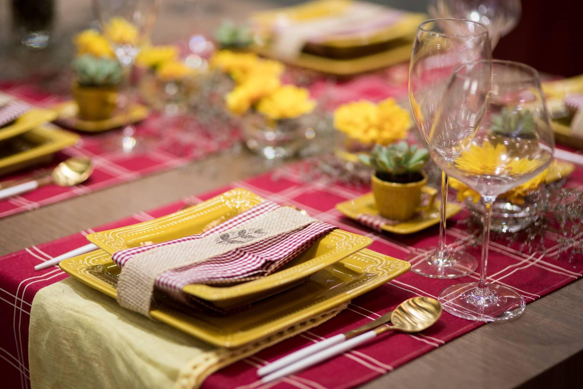 Caminhos de mesa e guardanapos em xadrez vermelho e branco contrastam com o amarelo da porcelana e dão um ar campestre à mesa. Os pratos são da linha Provence, da Oxford. Taças de cristal Athenas Classic, da Oxford Alumina Crystal. Foto: Henrique Peron