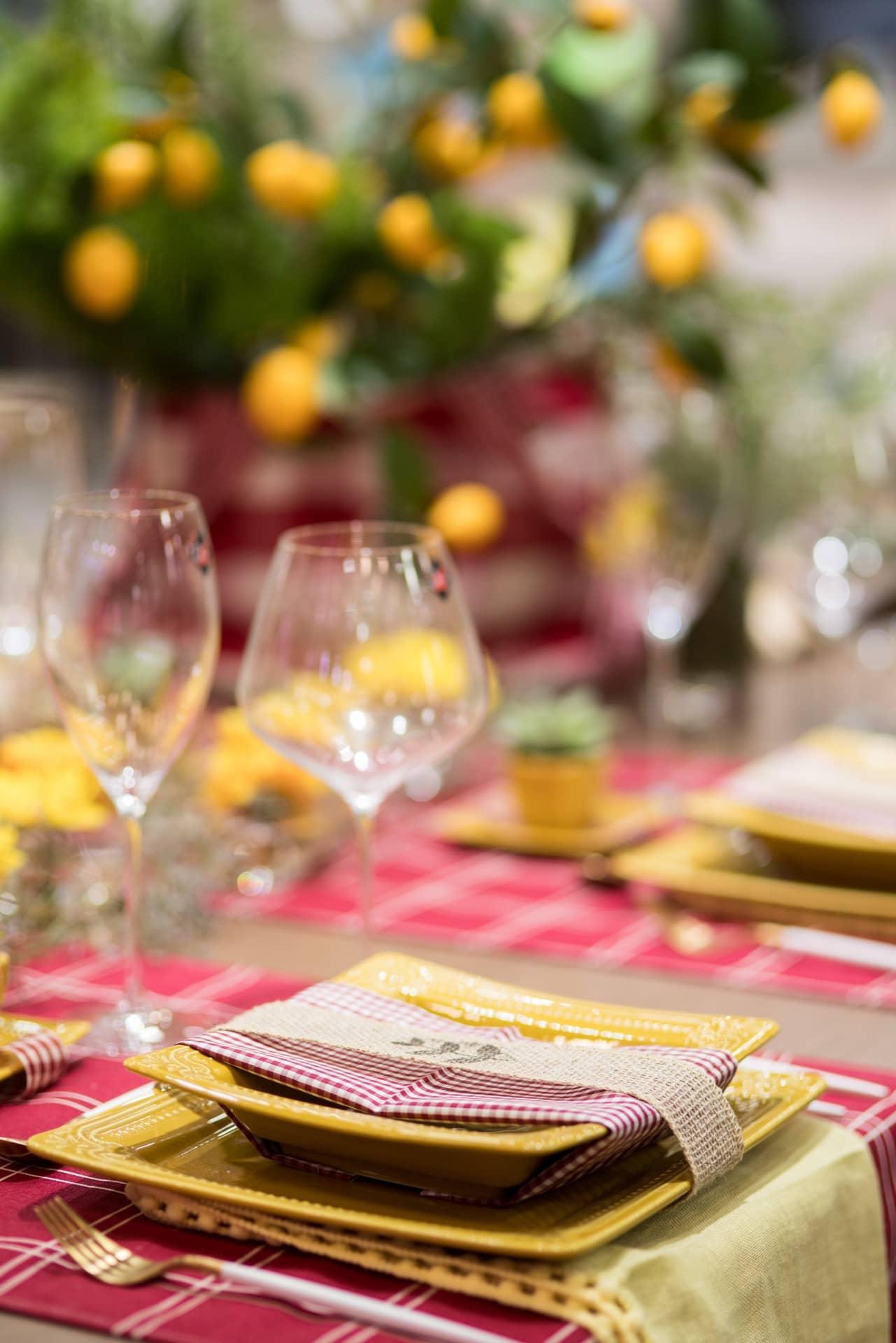 Guardanapos em xadrez Vichy, uma padronagem tipicamente francesa, abraçam os pratos de entrada. Uma fita de juta arremata o conjunto de louça provençal da Oxford. Embaixo dos pratos maiores, vai uma toalhinha amarela para criar mais um ponto de cor. Foto: Henrique Peron