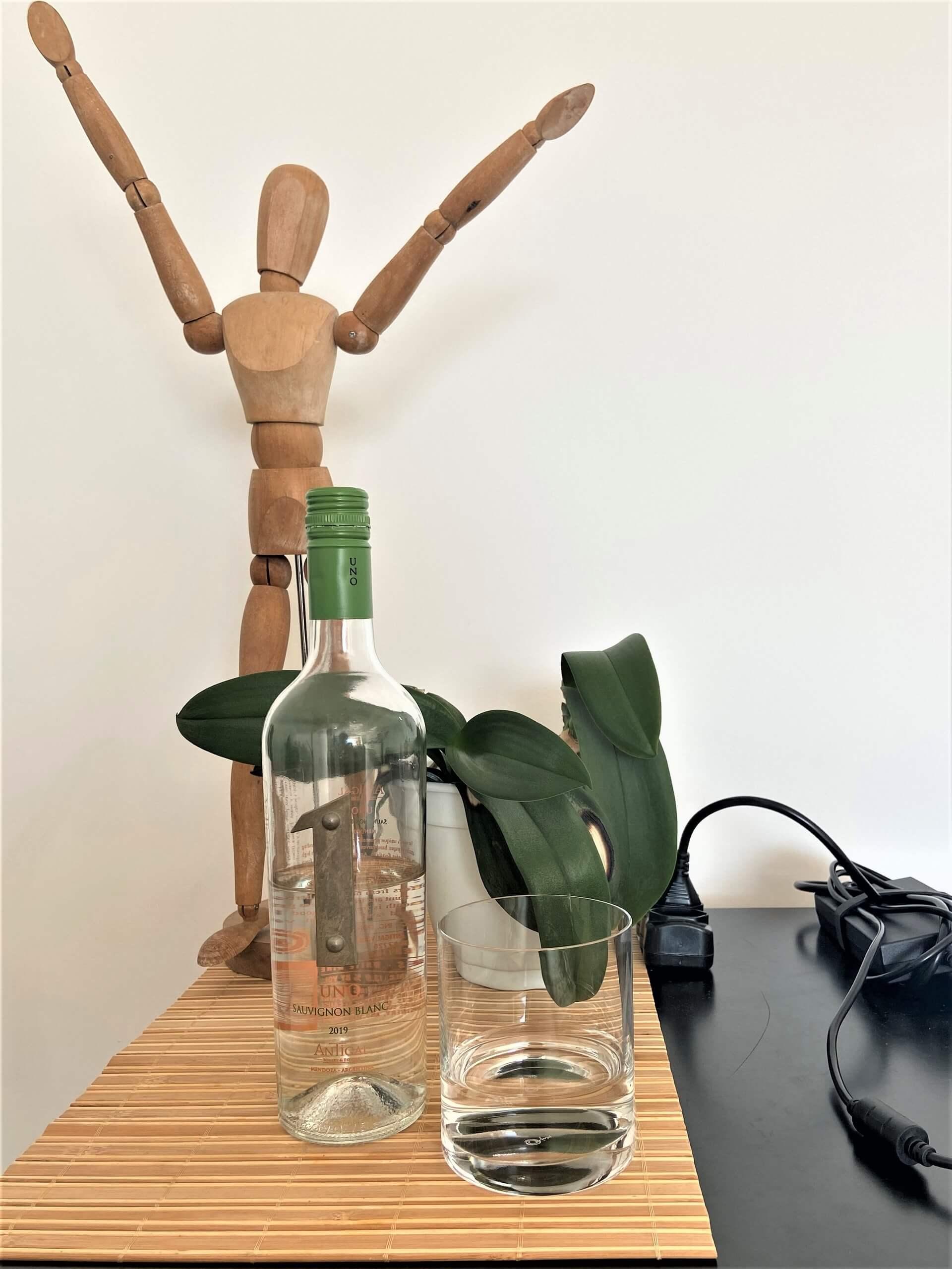 Garrafa de vinho que foi reaproveitada e utilizada como recipiente para a água e copo Oxford Clássico para On the Rocks.