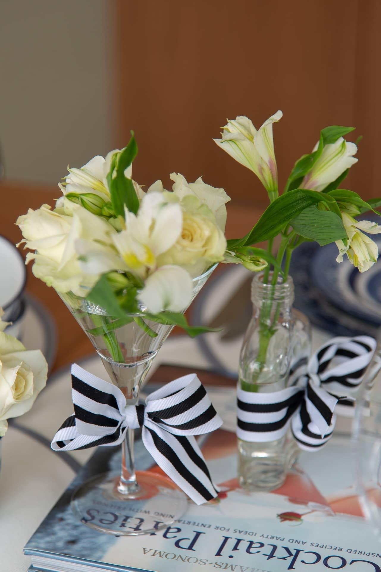 Imagem: No almoço de Dia das Mães, um centro de mesa caprichado faz toda a diferença! Para acomodar as flores -uma seleção de rosas e lisianthus brancos- usamos copos e vidrinhos de perfume. As fitas listradas dão um charme extra, enquantoo livro de decoração serve de base para o arranjo.Foto: Cacá Bratke