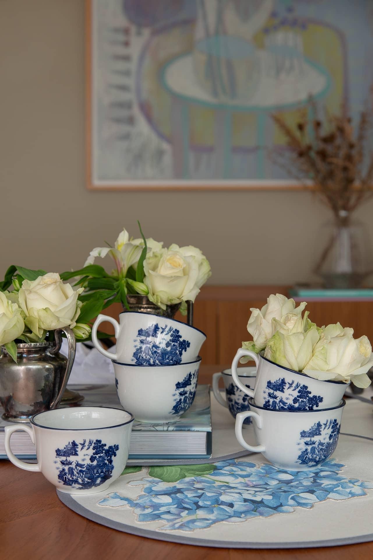Imagem: Até as xícaras da porcelana Blue Willow, da Oxford, entram na dança para homenagear a mamãe! Empilhadas em várias alturas, elas também ajudam a compor o arranjo encantador no centro de mesa. Foto: Cacá Bratke