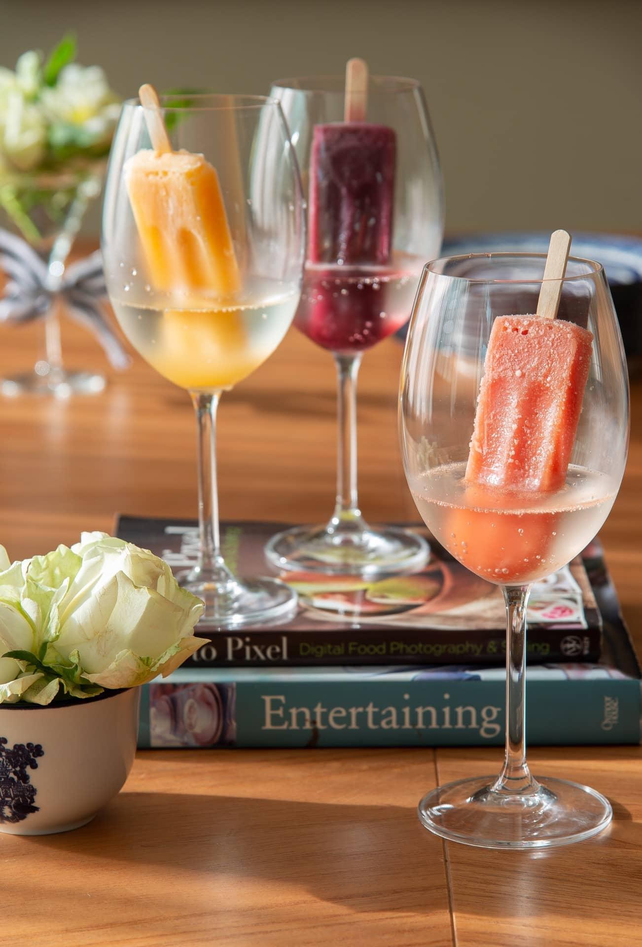 Imagem: O drinque para receber a família é fácil e refrescante: espumante com picolé de frutas, servido em taças Oxford Alumina Crystal. Os livros empilhados servem como bandeja. Foto: Cacá Bratke