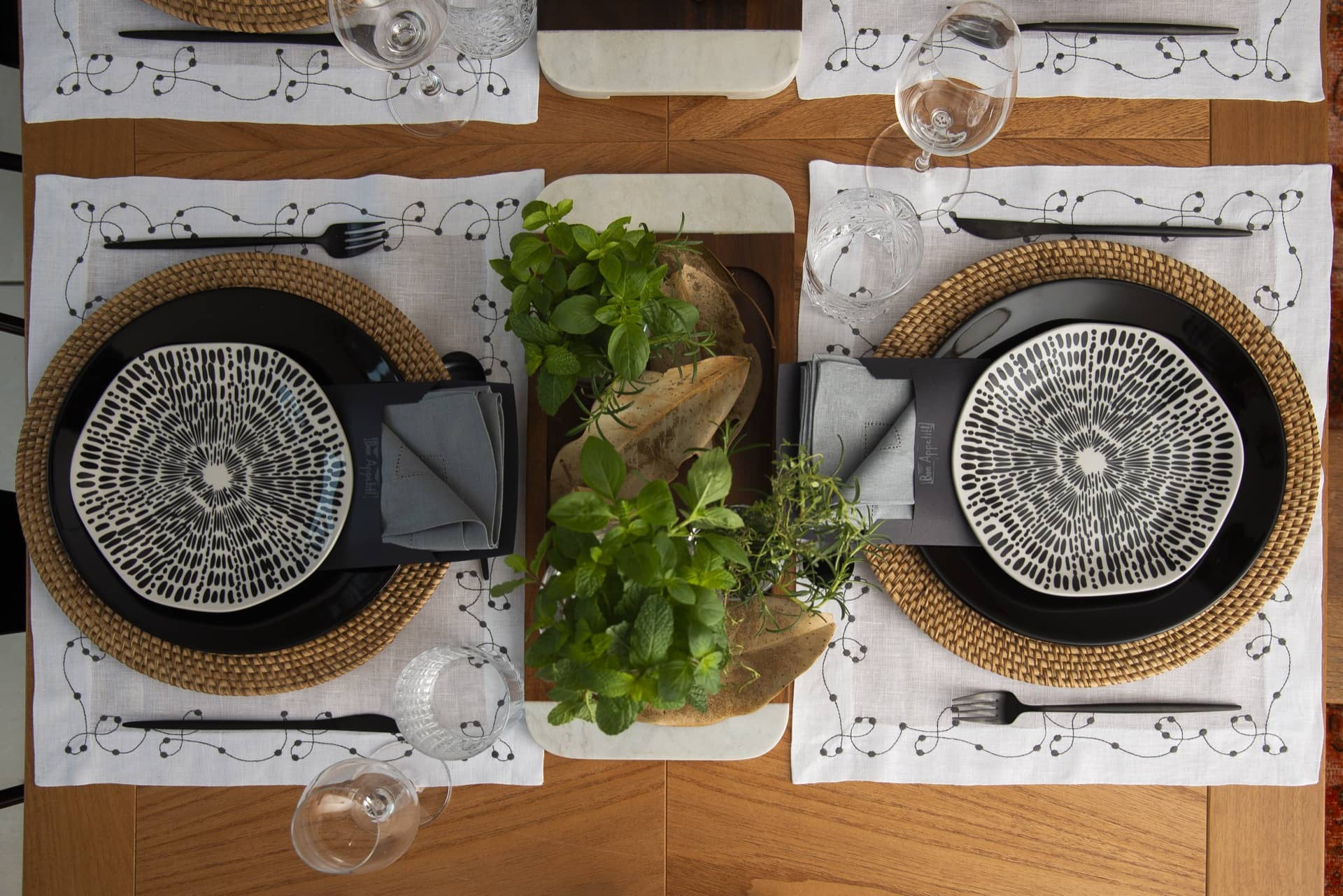 Uma boa ideia é coordenar louças de jogos diferentes. Aqui, usamos o prato de sobremesa Ryo Ink, que tem formas orgânicas e grafismos, e o prato de jantar Coup Black, na cor preta, ambos da Oxford. Por baixo, ficam: o sousplat de palha e o jogo americano com desenho de arabescos, da Artenamesa. Foto: Cacá Bratke