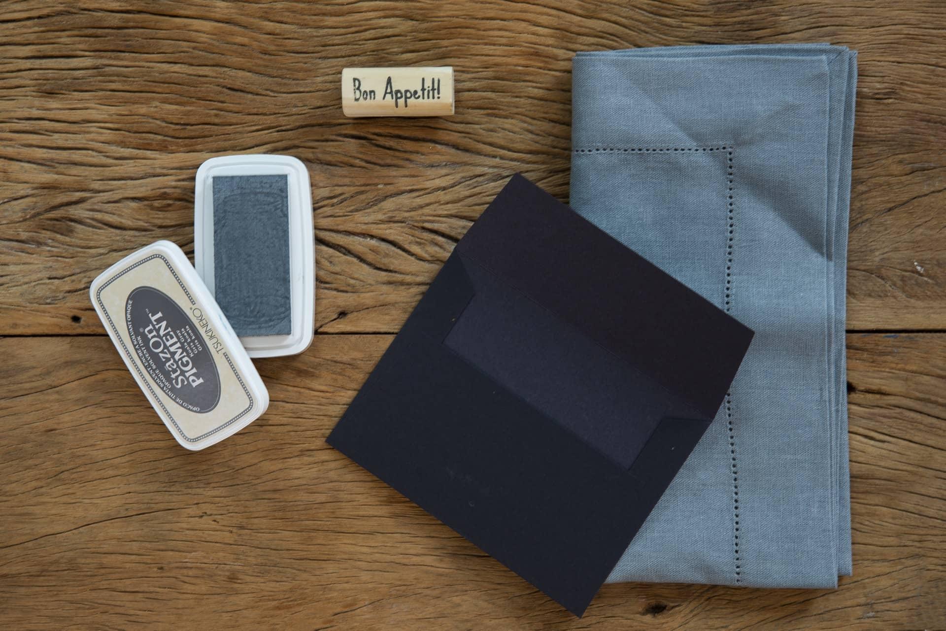 O guardanapo de linho cinza vai ficar elegante dentro do envelope preto. A tinta do carimbo tem o mesmo tom que o tecido. Foto: Cacá Bratike