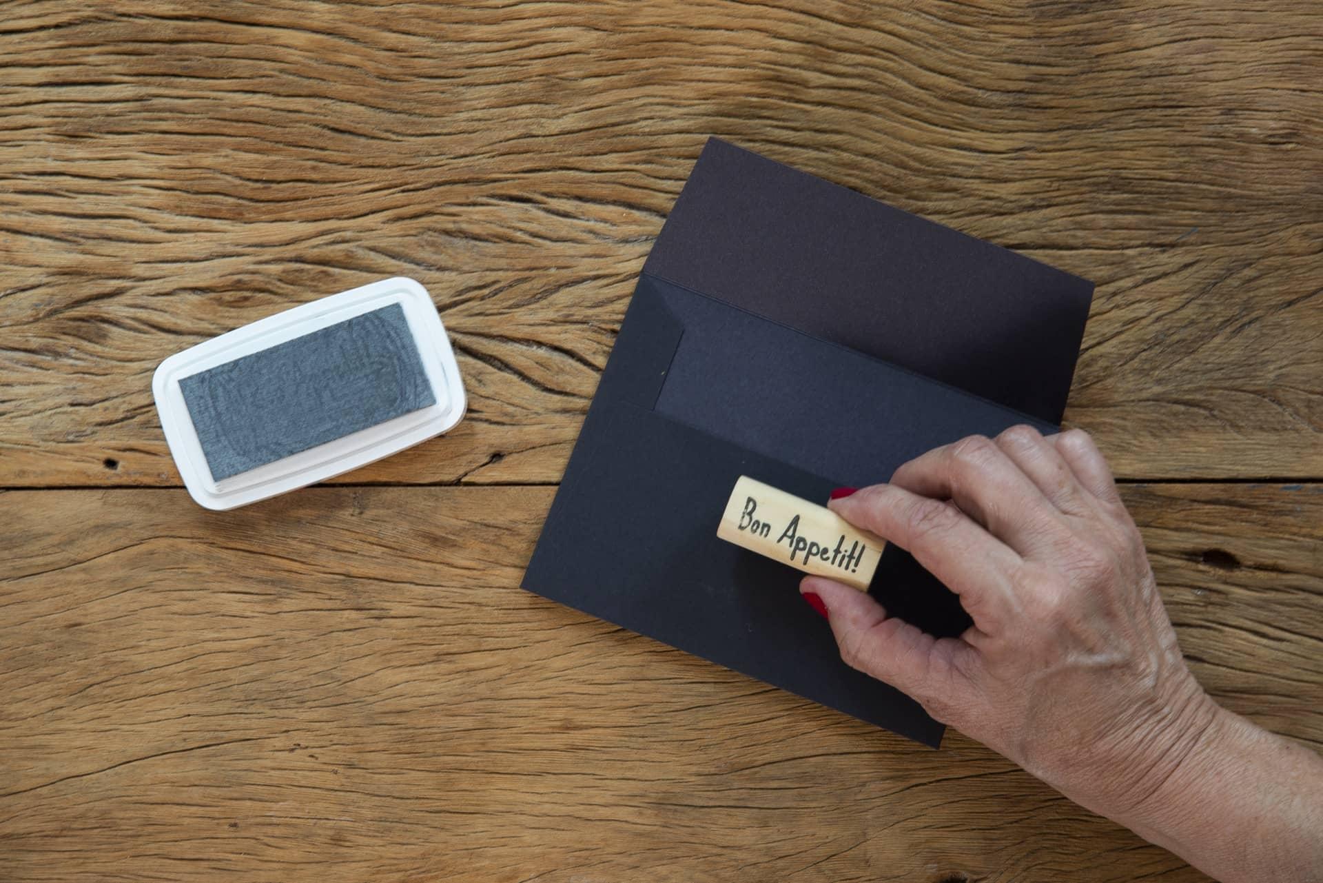 Passo 1: carimbe os envelopes na parte de trás, pois é o que ficará virado para os convidados. Foto: Cacá Bratke