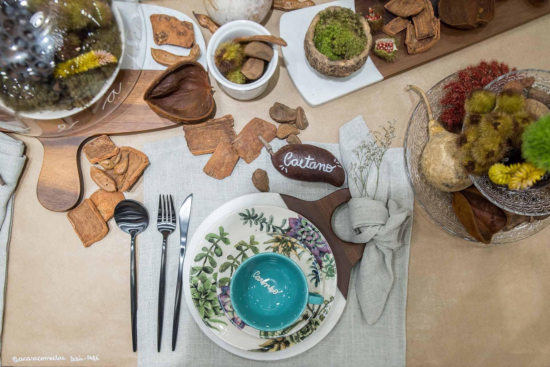 Texto: A semente de jatobá com a escrita do nome marca o lugar. Já as tábuas de madeira e mármore são dispostas em forma de caminho sobre a mesa. Foto: Henrique Peron.