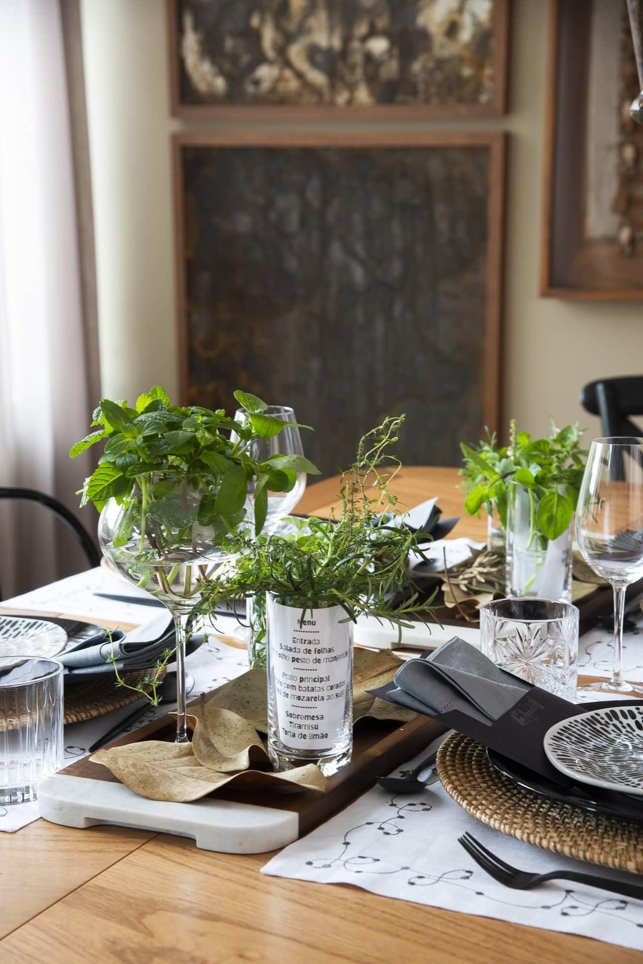 No centro da mesa, o arranjo é feito com ervas frescas, como hortelã, alecrim, tomilho e manjericão. Em pequenos maços, as ervas são dispostas em copos e taças de cristal daOxford Alumina Crystal. O conjunto fica sobre uma bandeja de madeira e mármore da Oxford, à venda em revendedores de todo país. Foto: Cacá Bratke
